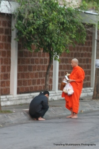 Monks make their rounds in the early morning to receive food and other items from the people.
